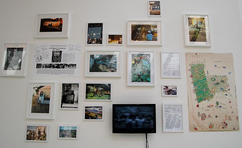 Immagine della parete con DVD su piccolo schermo e diverse foto e documenti incorniciati