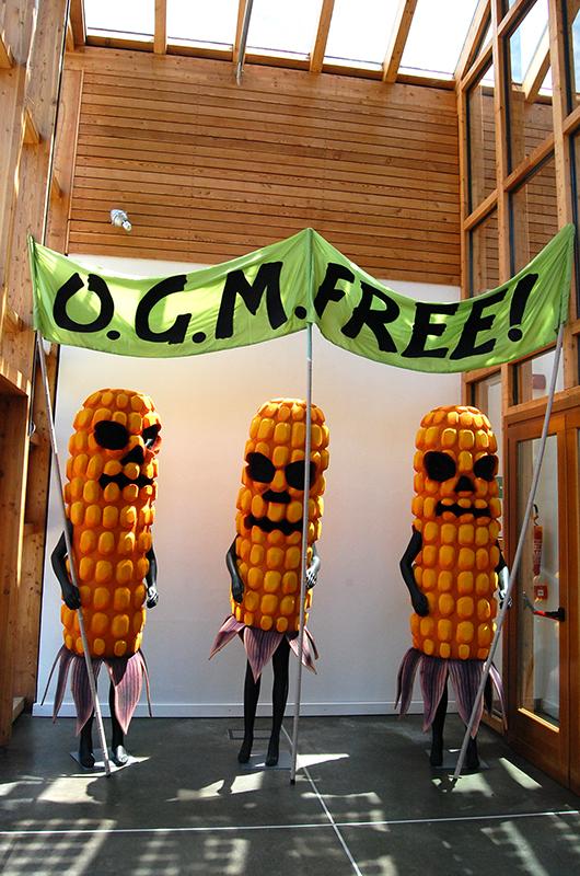 Immagine che propone tre pannocchie a dimensioni umane, indossate da tre manichini, portanti un cartello con la frase OGM Free