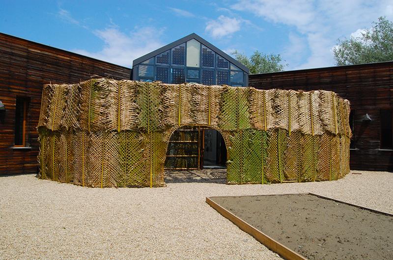 Fotografia di una enorme struttura fatta di bambu e foglie di palma che si erge nella corte del PAV