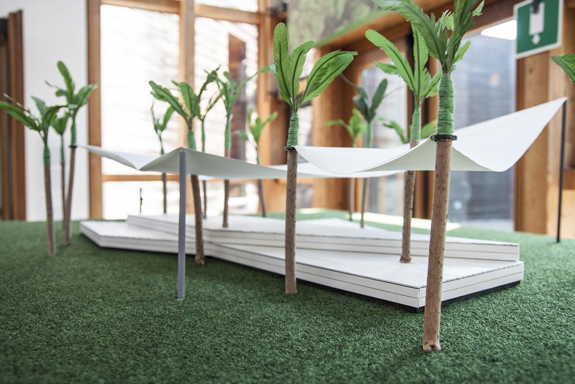 Plastico che rappresenta una serie di palme con teli ombreggianti e sedute sottostanti